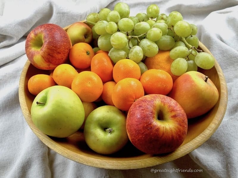wooden bowl full of fresh apples, grapes, and tangerines.