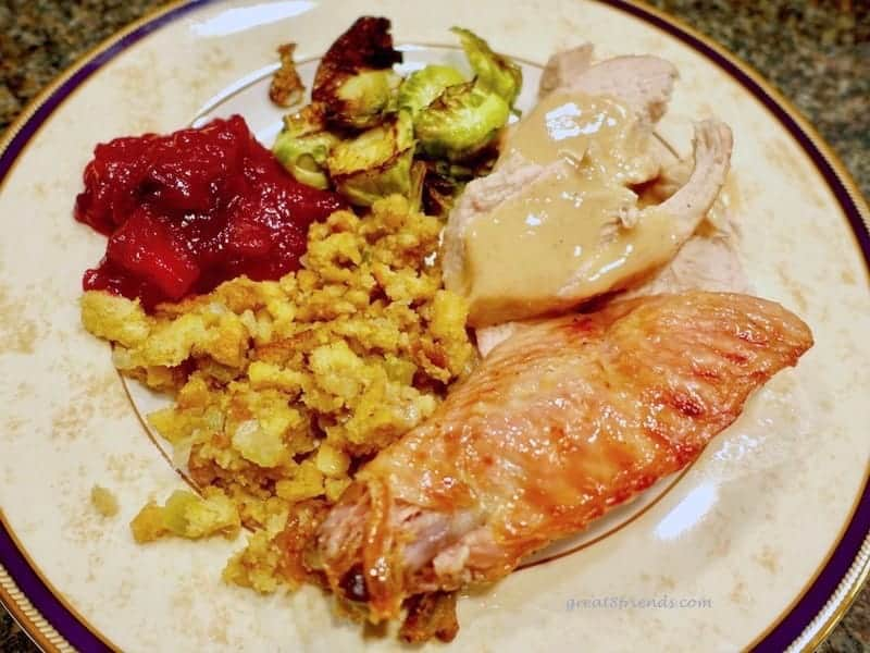 A plate of turkey, stuffing, cranberries.