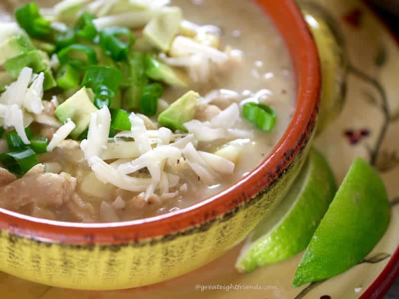 An unclose shot of a  bowl of White Cheddar Chicken Chili with two lime slices on the side.