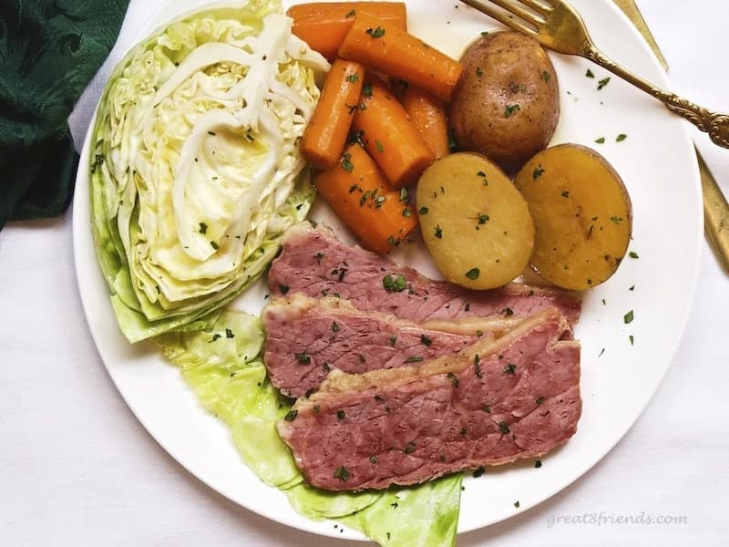 Overhead picture of corned beef dinner including cabbage, carrots and potatoes.