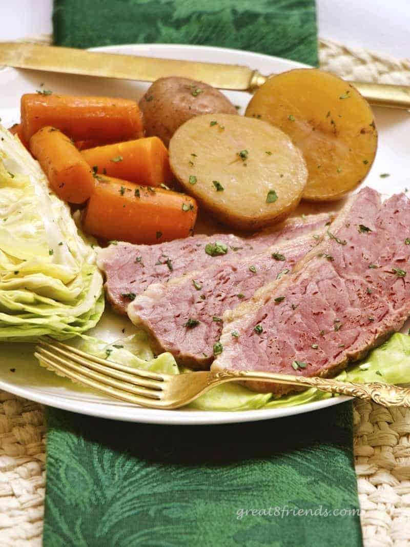 Vertical image of corned beef dinner including cabbage, carrots and potatoes with gold fork and green napkin.
