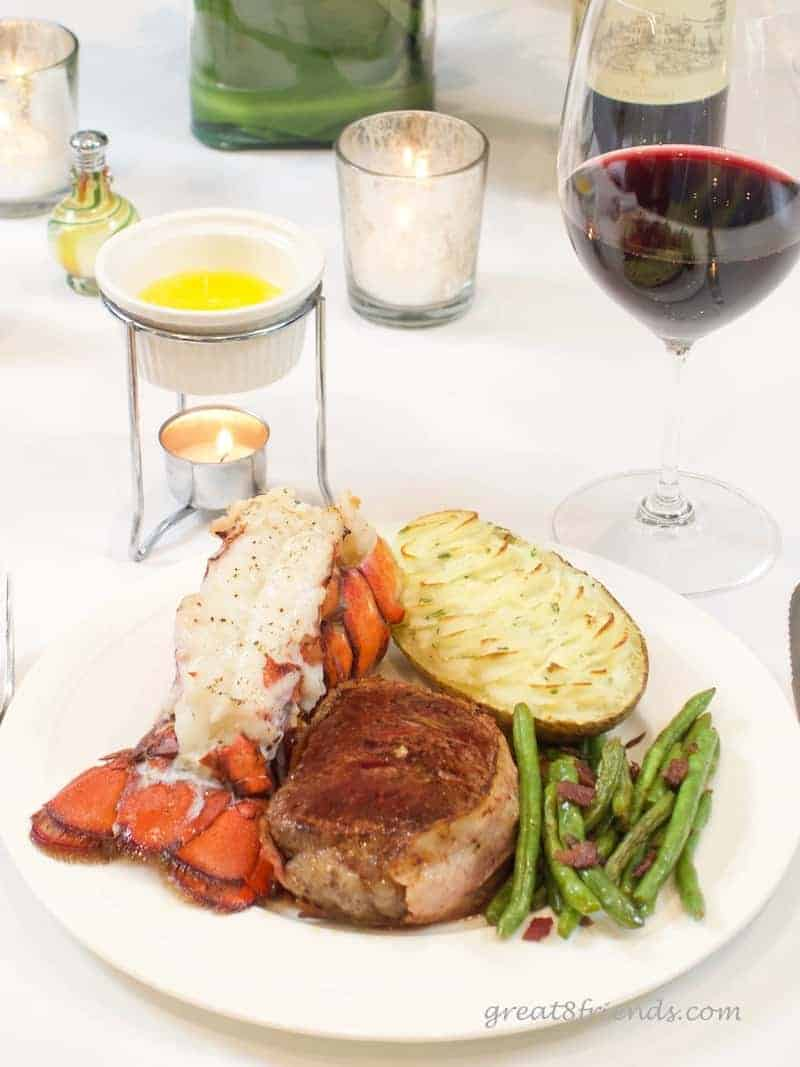 Meal of Lobster Tails with Clarified Butter, potato, filet, and green beans. With a glass of red wine and candlelight.