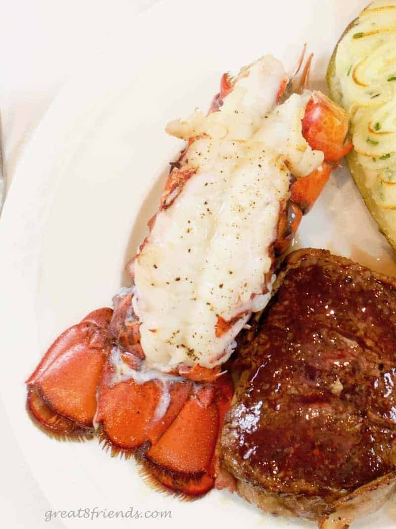 Overhead shot of a lobster tail on a white plate.