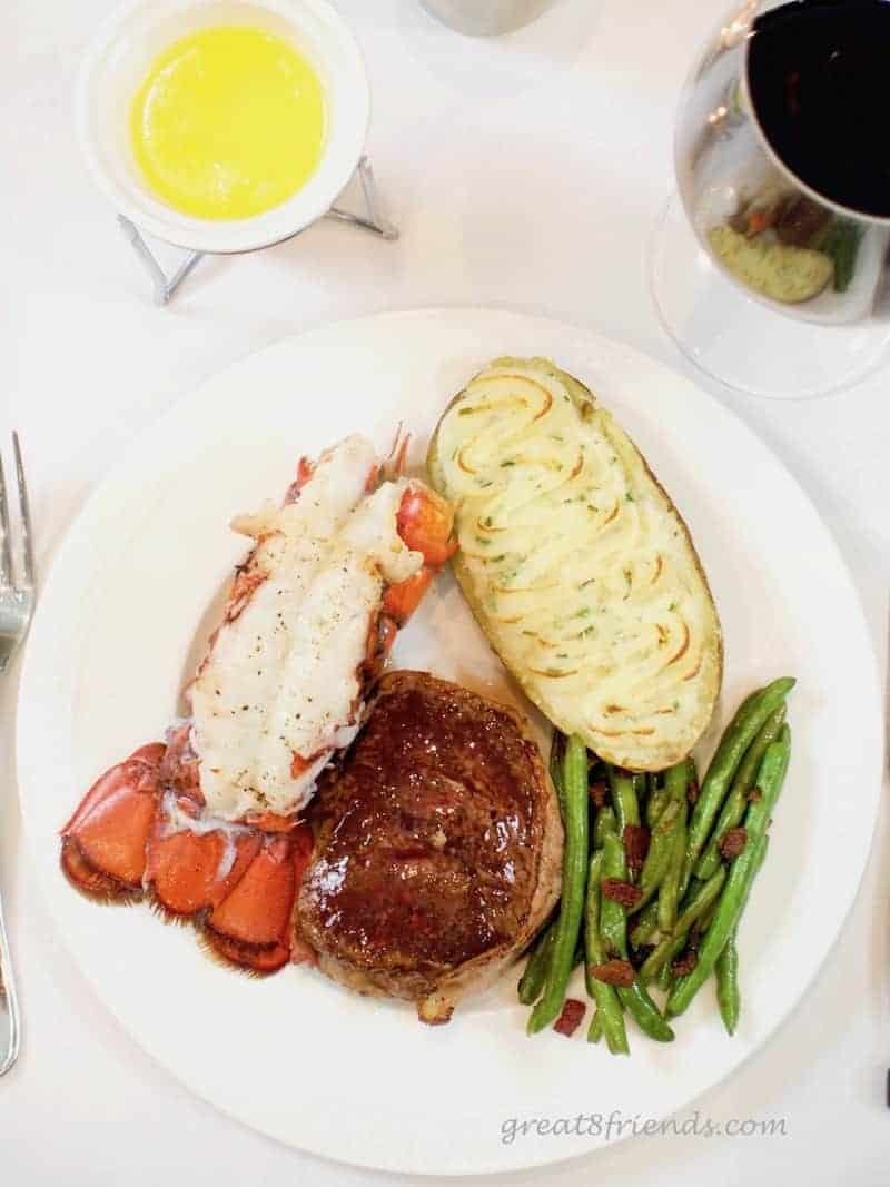 Overhead shot of dinner plate of surf and turf with potato and green beans.