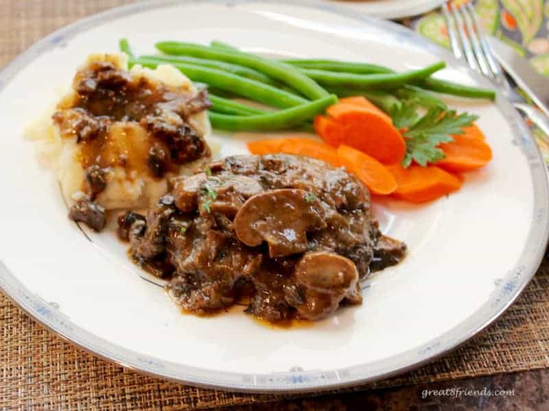 Salisbury Steak with Mushroom Onion Gravy served with carrots and green beans on a dinner plate.