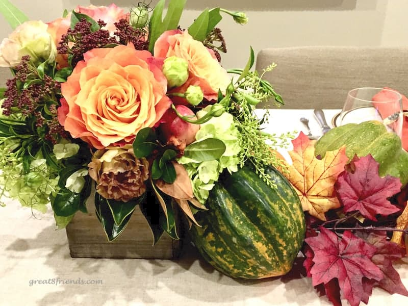 Thanksgiving centerpiece of yellow orange roses with greenery and a squash and some fall leaves.