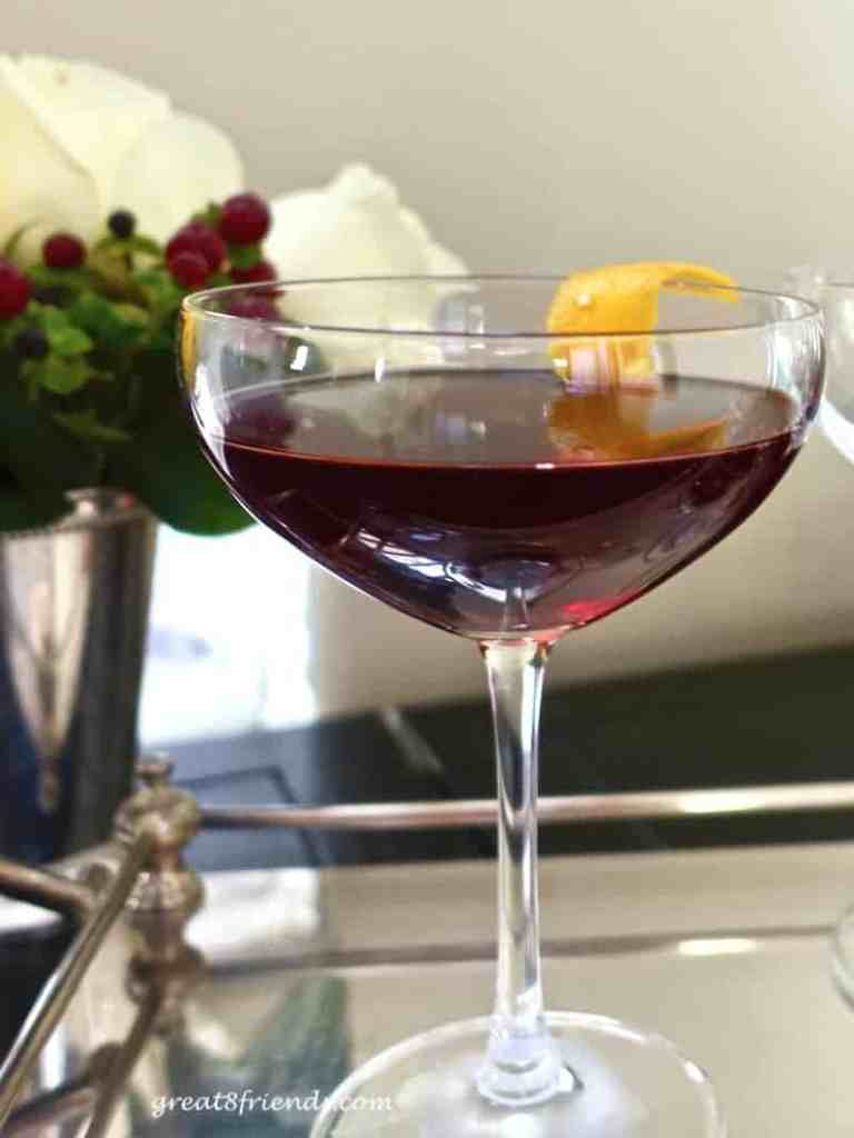 A Cherry Manhattan Cocktail in a coupe glass on a silver tray with an orange zest garnish.