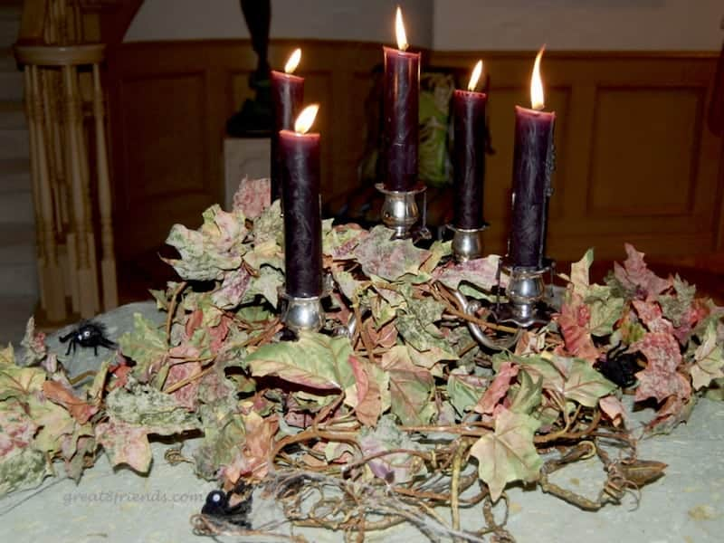 Burgundy candles on a candelabra surrounded by spooky fall leaves.