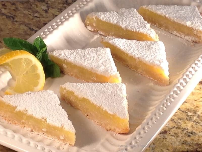 Lemon Bars with Shortbread Crust cut in triangles on platter.