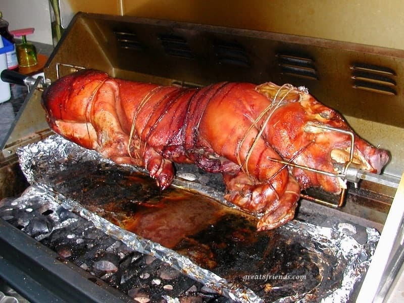 Whole pig roasting on a spit over the barbecue grill.