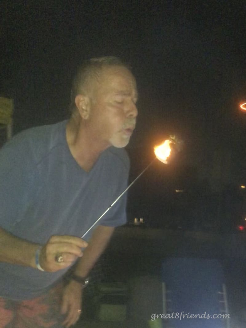 Joel blowing out the fire on a roasted marshmallow.
