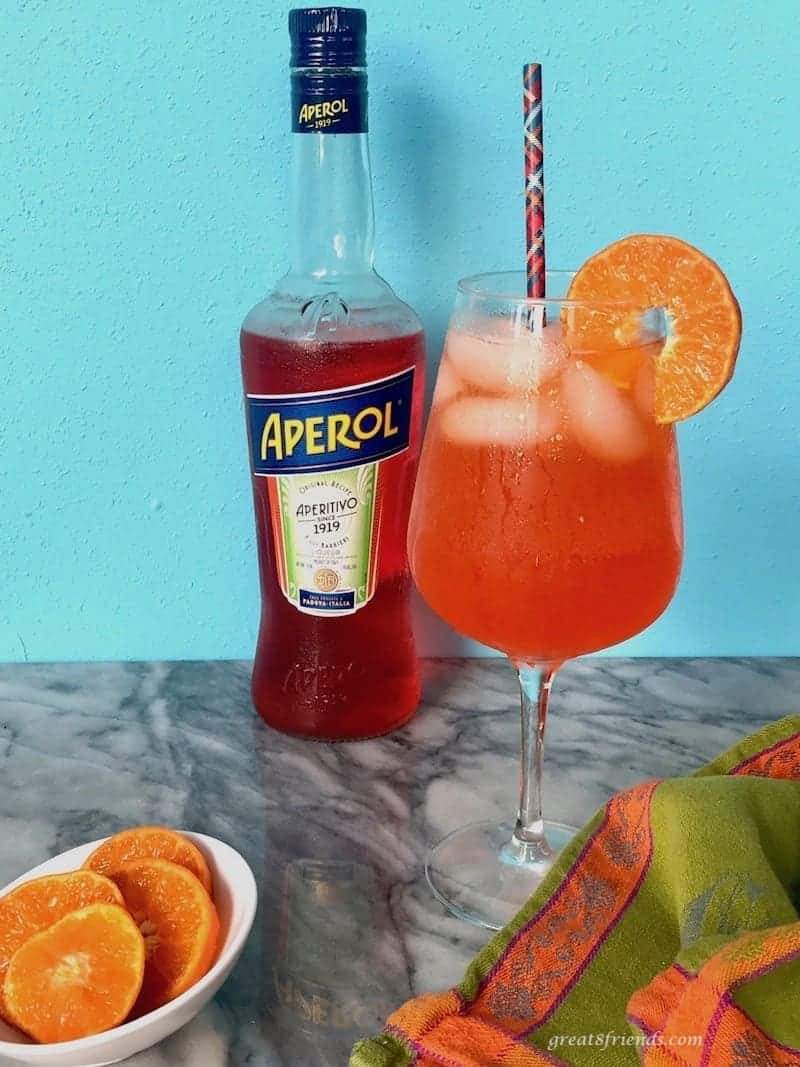 Aperol Spritz cocktail on a counter with a bottle of Aperol and sliced oranges in a bowl.