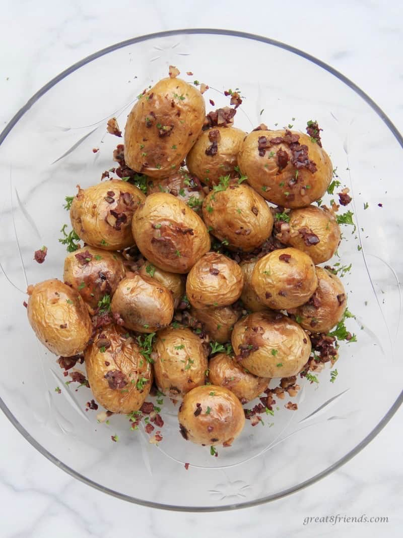 Poatatoes with an olive tapenade called dirty potatoes in a glass bowl.
