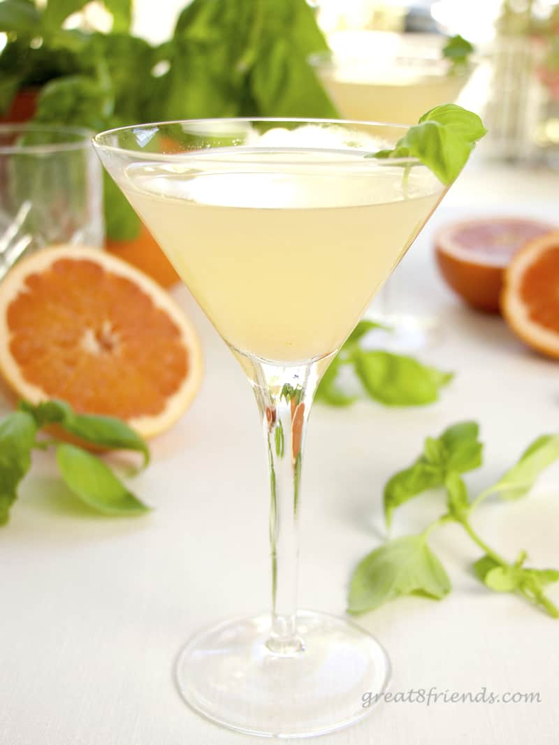 Grapefruit Basil Martini with cut oranges in the background.