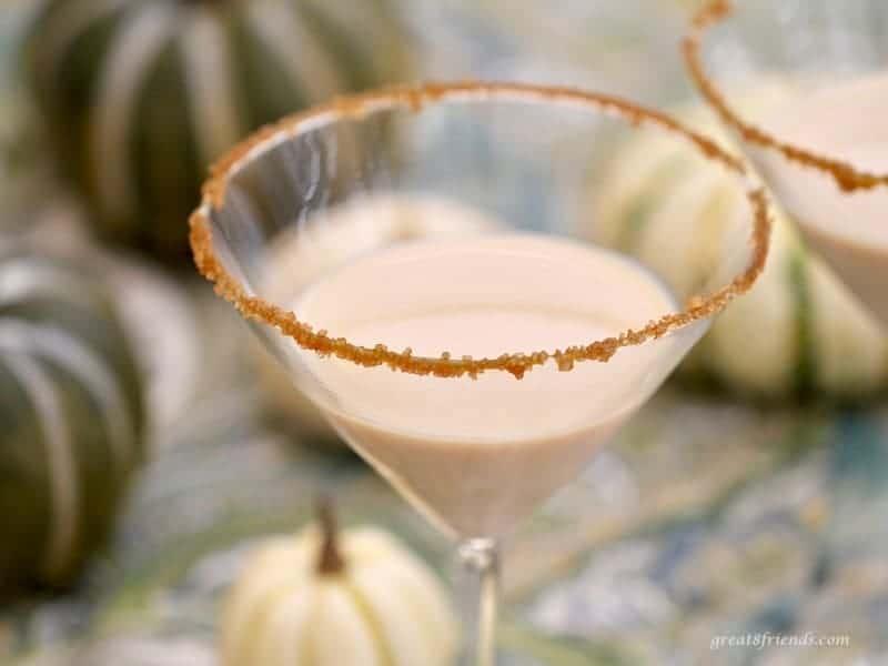 Upclose shot of a pumpkin martini with a caramel sugar rim.