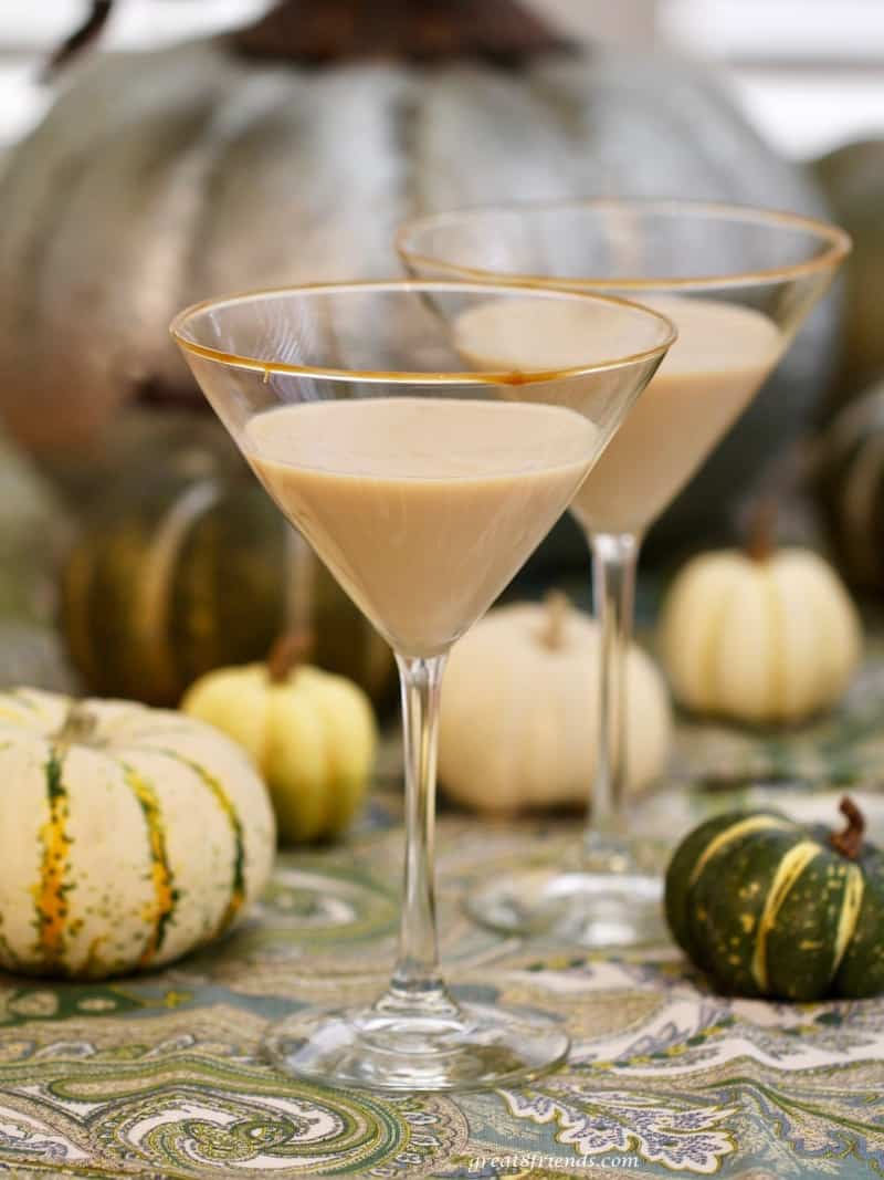 Two pumpkin martinis in stemmed martini glasses with small pumpkins surrounding.