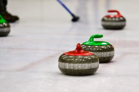 Granite curling stones on ice - DepositPhotos.com