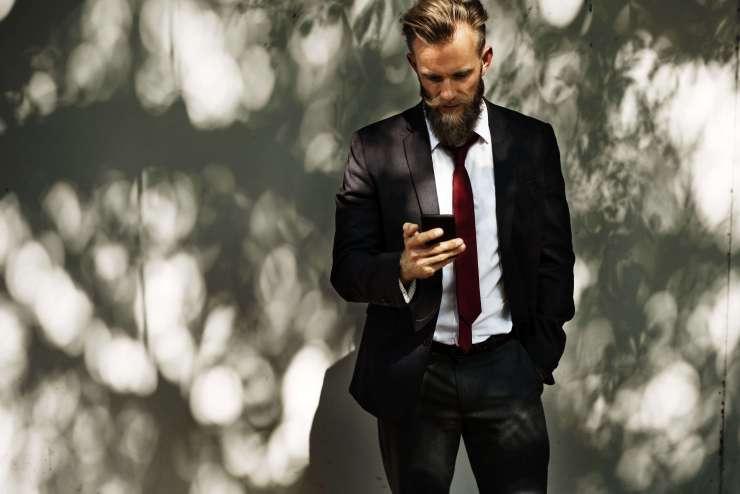 man met baard en mobiel