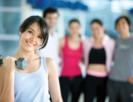 woman at the gym exercising with free weights in front of a group