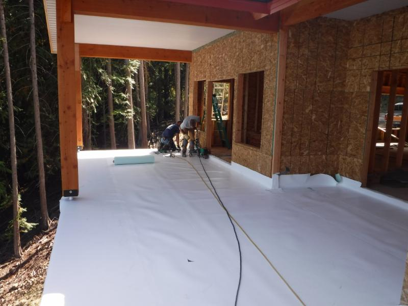 A waterproof membrane seals the upper deck. A decorative concrete  surface will follow, creating a dry roof over the patio below.