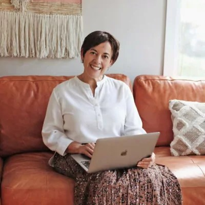 A woman sitting on a couch holding a computer on her lap