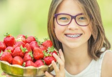young girl with braces holding strawberries