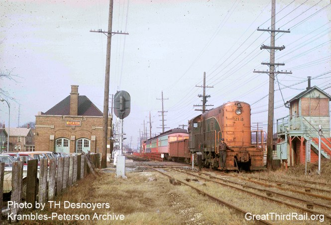 From www.thegreatthirdrail.org: The end has come for the Roarin' Elgin. The rails have rusted over and the hallmark of the railroad, the third rail, has already been taken off of the third rail chairs. Fortunately all isn't lost. On March 24, 1962, we see EJ&E 212 hauling several CA&E cars past the Wheaton station and Main Street to be preserved at RELIC (today's Fox River Trolley Museum). Photo by TH Desnoyers, from the Krambles-Peterson Archive