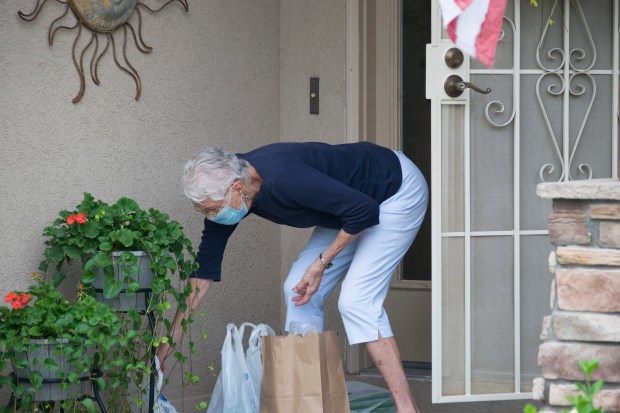 GREELEY, CO, July 30: Sylvia Bedingfield stoops to pick up her groceries outside her Greeley home Thursday, July 30. The groceries were delivered to her door by a service called 60+ Rides, of which Bedingfield's daughter, Janet Bedingfield, serves as director. Cuyler Meade/Staff reporter