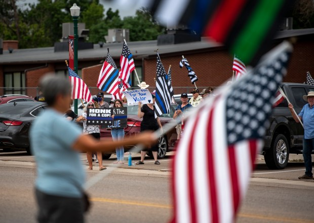EATON, CO - JULY 25:Demonstrators on both sides of Collins Street wave flags and hold signs during a Defend the Police rally at Town Square Park in Eaton July 25, 2020. The driver of a red SUV that drove by and flipped off rally goers returned and drove off of Collins Street and onto the grass on the south side of the street before driving back onto the road and heading west, nearly hitting rally goers in the process. The suspect is in Eaton Police custody, according to officers at the scene. (Alex McIntyre/Staff Photographer)