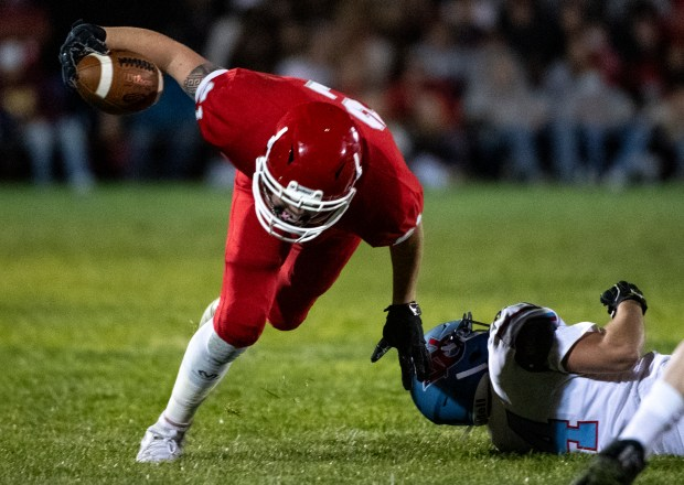 EATON, CO - OCTOBER 09:Eaton's Gage Butler (21) loses his footing after nearly breaking a tackle by Weld Central's Jeremiah Dreher (24) during the Eaton Reds football season opener against the Weld Central Rebels at Eaton High School in Eaton Oct. 9, 2020. The Reds defeated the Rebels 49-6. (Alex McIntyre/Staff Photographer)