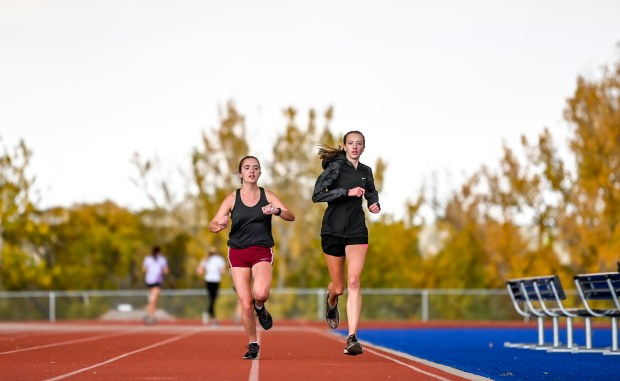 GREELEY, CO - OCTOBER 14:Frontier Academy cross country athletes Emma Murphy, left, and Audrynn Street run a 300 meter run during cross country practice on the track at Frontier Academy Secondary School in Greeley Oct. 14, 2020. (Alex McIntyre/Staff Photographer)