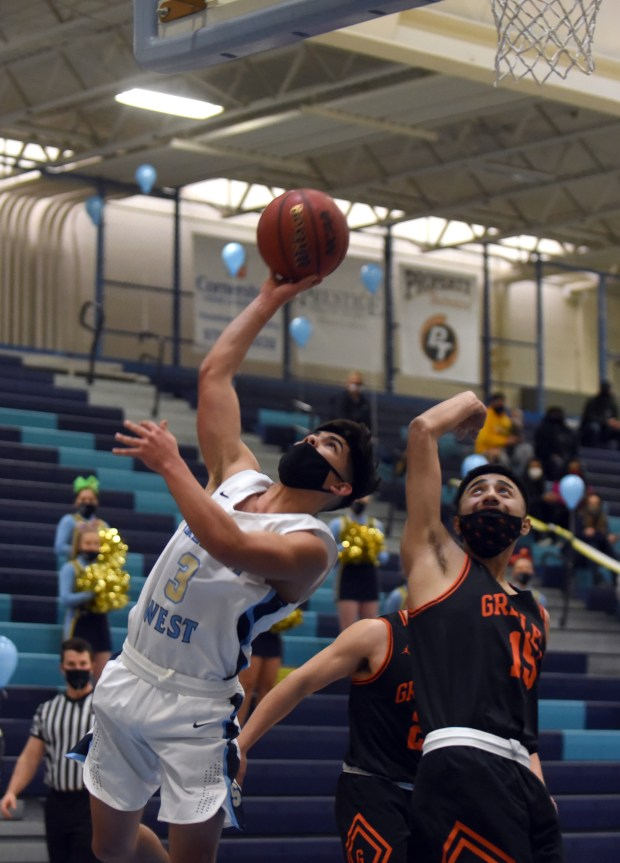 Greeley West's Nate Hill makes a shot as he passes by Greeley Central's Juan Espinoza during the game Monday night at Greeley West High School. (For the Tribune/Joshua Polson)