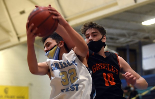 Greeley West's Alejandro Hernandez grabs a rebound along with Greeley Central's Ben Kingsford during the game Monday night at Greeley West High School. (For the Greeley Tribune/Joshua Polson)