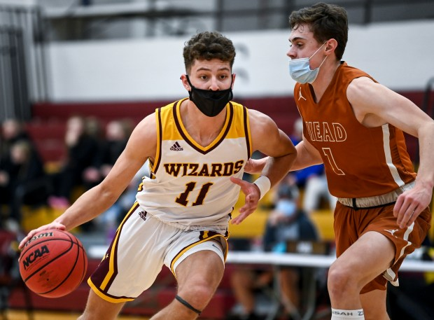 WINDSOR, CO - FEBRUARY 17:Windsor's Jaden Kennis (11) slips by MeadÕs Nick Basson (1) during the Mead Mavericks boys basketball game against the Windsor Wizards at Windsor High School Feb. 17, 2021. The No. 2 Windsor Wizards defeated the No. 1 Mead Mavericks 69-59. (Alex McIntyre/Staff Photographer)