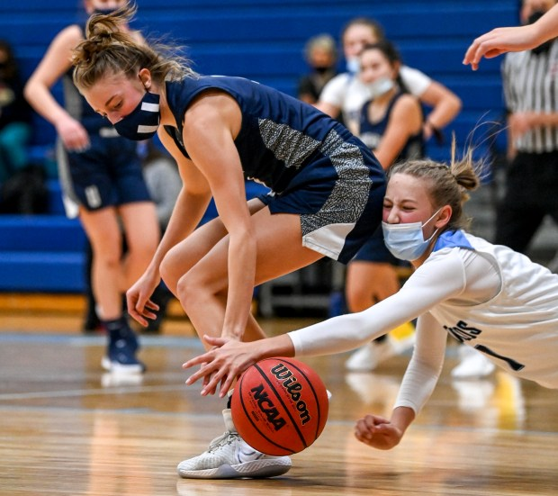 KERSEY, CO - FEBRUARY 13:Platte Valley's Andi Schissler (1) falls as University's Kylie Kravig (4) scrambles for the ball during the Platte Valley Broncos girls basketball game against the University Bulldogs at Platte Valley High School in Kersey Feb. 13, 2021. The Broncos defeated the Bulldogs 40-36. (Alex McIntyre/Staff Photographer)