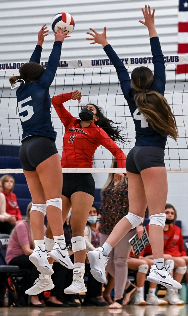 GREELEY, CO - APRIL 06:Eaton's Jisell Chumacero (11) attacks as University's Kylie Williams (5) and University's Aesha Alrashed (4) leap to block during the University Bulldogs volleyball game against the Eaton Reds at University Middle School in Greeley April 6, 2021. The Reds defeated the Bulldogs 3-1. (Alex McIntyre/Staff Photographer)