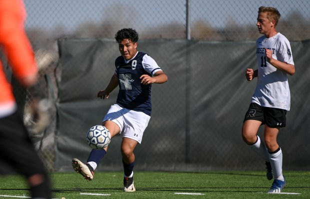 GREELEY, CO - APRIL 03:Northridge's Juan Beltran (9) kicks ahead of Roosevelt's Titus Larson (11) during the Northridge Grizzlies boys soccer match against the Roosevelt Rough Riders at District 6 Soccer Stadium in Greeley April 3, 2021. (Alex McIntyre/Staff Photographer)