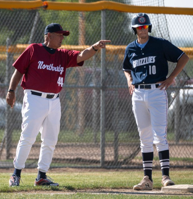 GREELEY, CO - JUNE 10:Northridge head coach Mike Huston speaks with Northridge's Nick Garland (10) as Garland stands at third base during the Northridge Grizzlies baseball game against the Silver Creek Raptors at Darryl Kile Field in Greeley June 10, 2021. The Grizzlies defeated the Raptors 9-7. (Alex McIntyre/Staff Photographer)