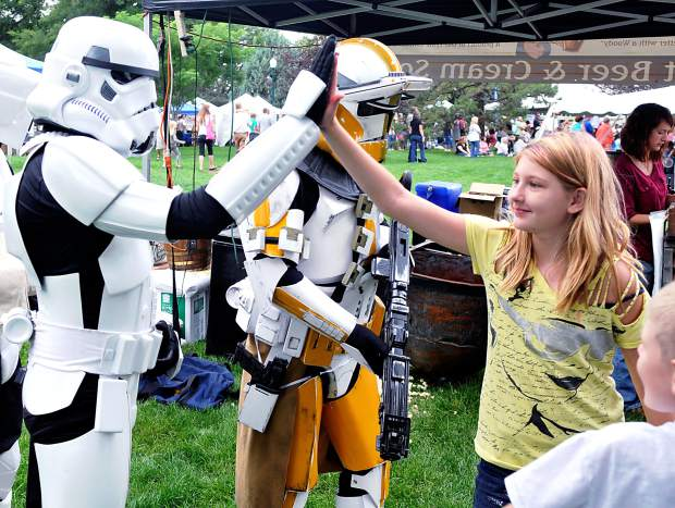 Nick Kenny, playing the role of a stormtrooper, high-fives Alexis Jones, 10, as they both explore the Greeley Arts Picnic on Saturday in Lincoln Park.