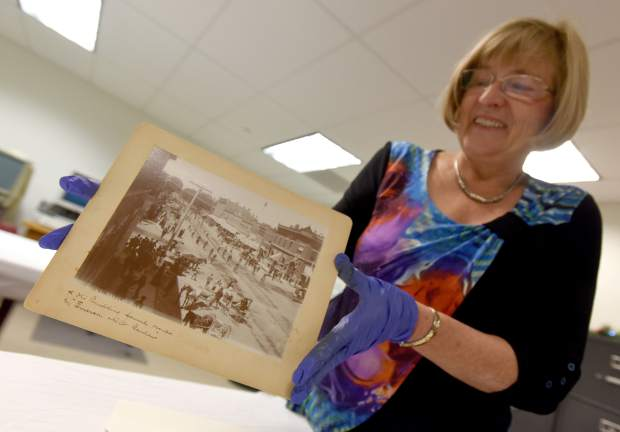 Peggy Ford Waldo smiles as she pulls one of the photos used in a book she wrote with the help of the Greeley History Museum on Monday at the Museum, 714 8th St. Ford Waldo has worked at the museum to help document and preserve the history of Greeley since 1979.