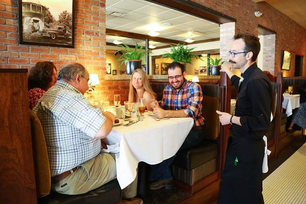Bryan Guercioni, a waiter at The Greeley Chophouse, talks with customers during the Easter Sunday brunch hosted by the restaurant. Following the brunch, the Chophouse transitioned back into its normal dinner service for the remainder of the night.