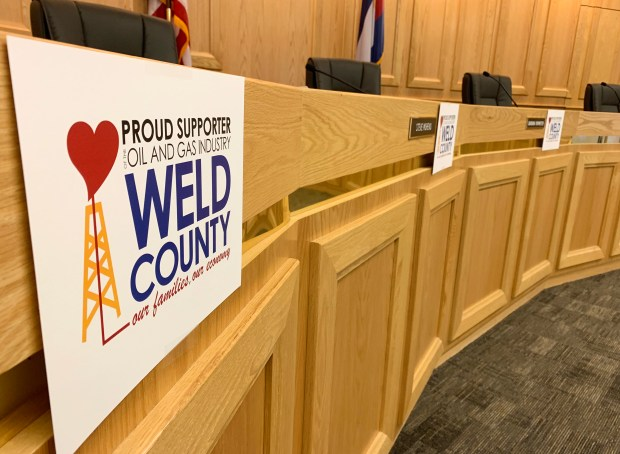 Signs denoting the Weld County Commissioners' support of the oil and gas industry hang next to their names at Monday morning's meeting, where the commissioners signed a proclamation in support of oil and gas. (Emily Wenger/ewenger@greeleytribune.com)
