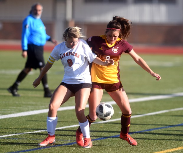 Windsor's Carty Kingsbury struggles to get the ball from Mead's Peyton Fox during the game Thursday at H.J. Dudley Field in Windsor. Windsor went on to win 4-0.