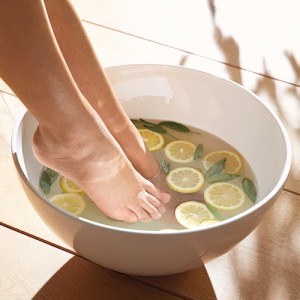 Pieds de femme dans une bassine avec rondelles de citron