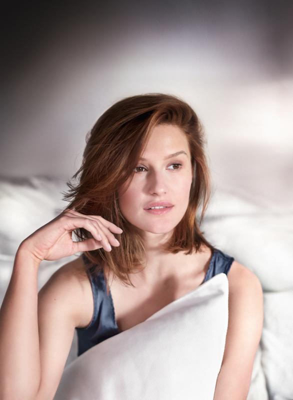 Femme qui s'éveille dans son lit, fraîche comme une rose.