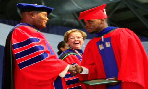Former Vice President and Founder of American University of Nigeria, Yola (AUN) Atiku Abubakar congratulating Ahmad A Abubakar a graduate  of AUN 2014 Class at the 6th Commencement Ceremony of AUN in Yola