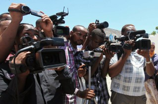 Somali journalists demonstrate against an article appearing in the British paper The Guardian calling them corrupt, in capital Mogadishu October 18, 2012. A journalist holds up a picture of the article's author Jamal Osman (R). REUTERS/Feisal Omar (SOMALIA - Tags: CIVIL UNREST POLITICS)