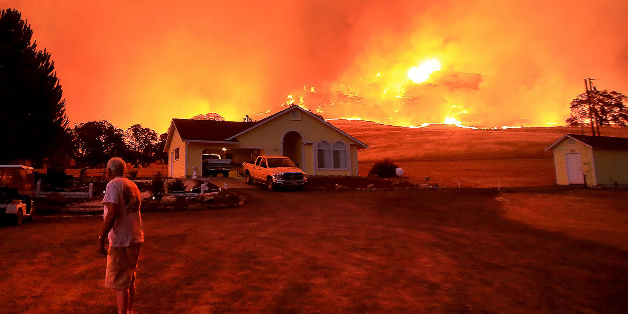man in front of house with wildfire in surrounding landscape