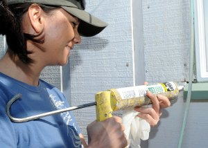 woman applying caulk sealant around window