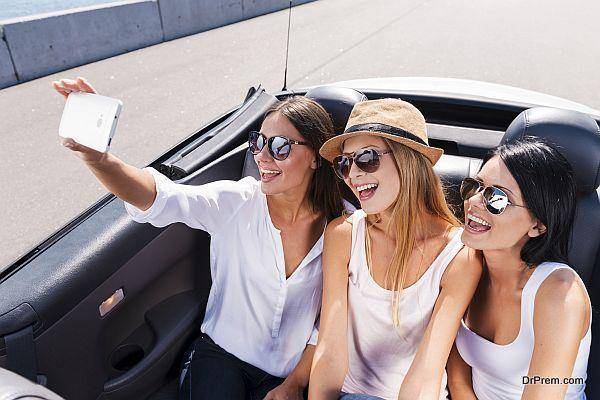 Capturing fun. Top view of three beautiful young women enjoying